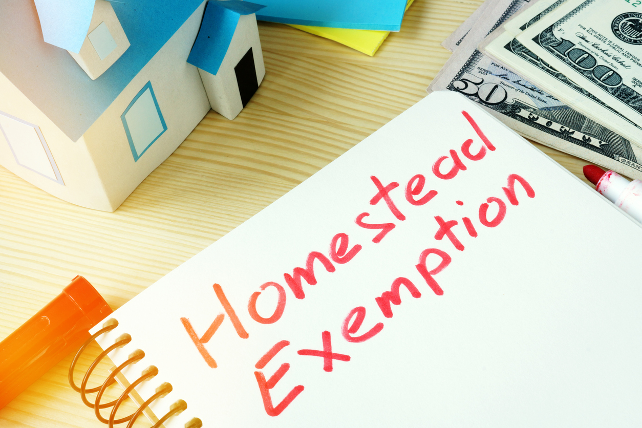 Homestead exemption written on note card with model house and money
